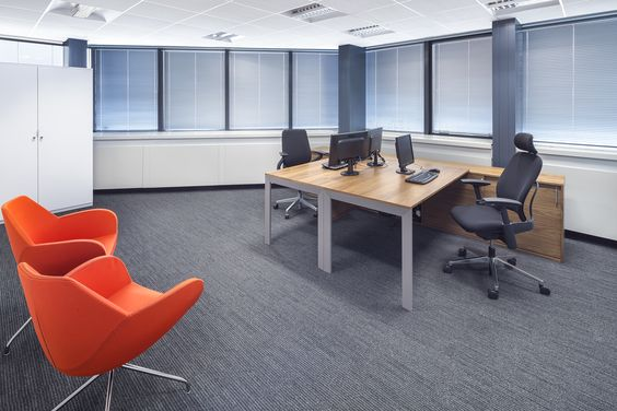 biuro z szarą wykładziną i pomarańczowym fotelem